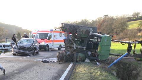 Beschädigter PKW steht neben einem liegenden Traktor