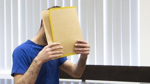 Der Angeklagte versteckt sein Gesicht hinter einer Akte