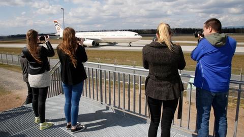 Personen auf der Plattform fotografieren ein Flugzeug
