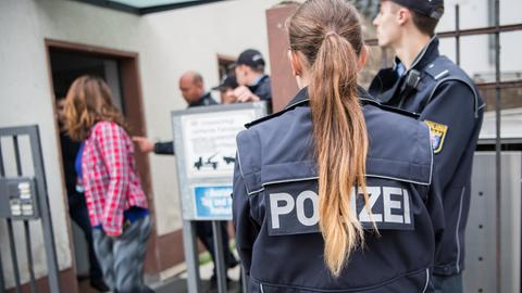 Eine Anwohnerin verlässt erst nach massivem Einsatz mehrerer Polizeibeamte ihre Wohnung im Sperrgebiet.