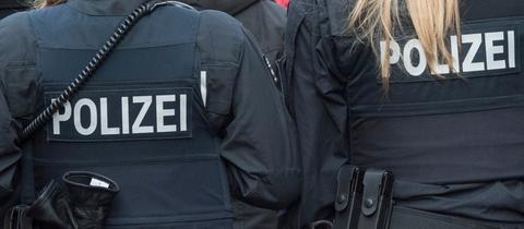 Rücken von Polizist und Polizistin