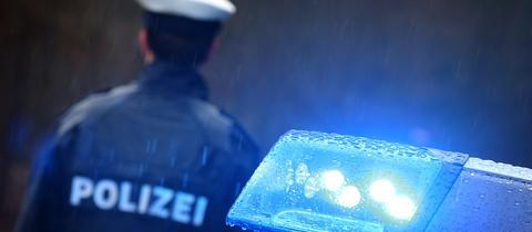 Polizist von hinten neben einem Streifenwagen, dessen Blaulicht leuchtet.
