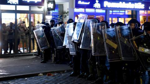 Polizeikräfte ziehen sich in Hamburg im Schanzenviertel vor den Demonstranten zurück, während sich Passanten hinter den Scheiben eines Restaurants in Sicherheit bringen.