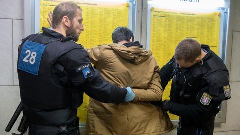 Ein Polizist hält einen Mann an den Händen fest, während ein anderer dessen Taschen durchsucht. Die drei Stehen vor der Abfahrtstafel am Hauptbahnhof.