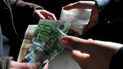 Geldscheine werden im Tausch gegen ein Drogentütchen übergeben
