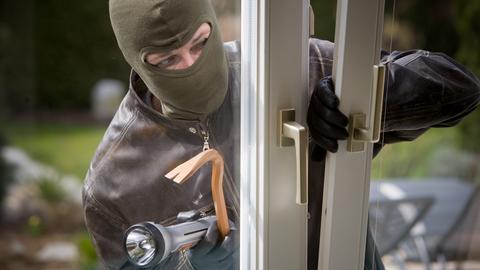 Maskierter Einbrecher öffnet ein Fenster
