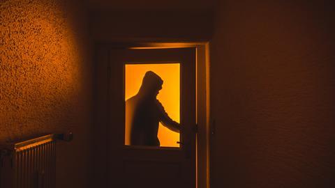 Schatten eines Mannes hinter einer Tür