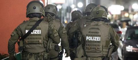 """Mehrere SEK-Einsatzkräfte in einer Gruppe von hinten fotografiert. Auch ihren Rücken steht """"POLIZEI""""."""