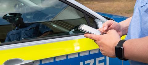 Polizist tippt etwas in ein Smartphone, im Hintergrund steht ein Streifenwagen