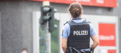 Eine Polizeibeamtin vor der Sparkasse im Bahnhofsviertel.