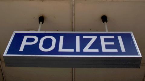 """Ein Schild mit der Aufschrift """"POLIZEI"""" hängt von der Decke eines Gebäudes."""