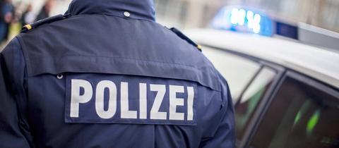"""Polizist von hinten, auf der Jacke steht in großen Lettern """"Polizei"""". Daneben ein Polizei-Auto mit Blaulicht. Sujetbild."""
