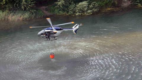 Polizeihubschrauber IBIS1 bei der Aufnahme von Löschwasser