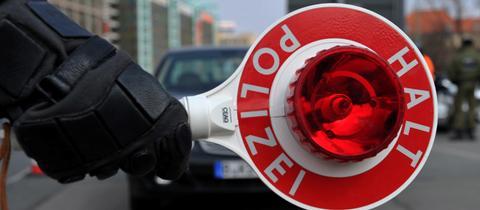 """Polizei hält eine Kelle mit der Aufschrift: """"Halt, Polizei""""."""