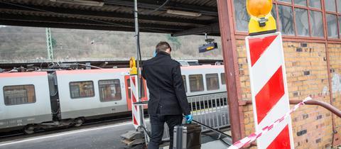 Ein Beamter der Spurensicherung auf dem abgesperrten Bahnsteig in Herborn.