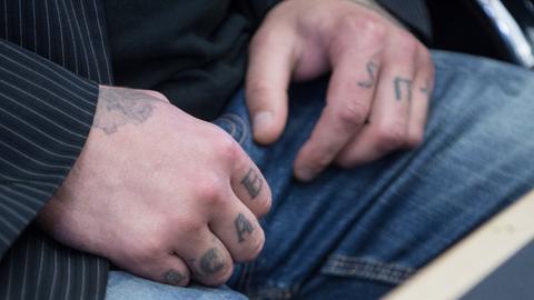 Die tätowierten Hände des wegen Mordes an einem Polizisten angeklagten 27-Jährigen.