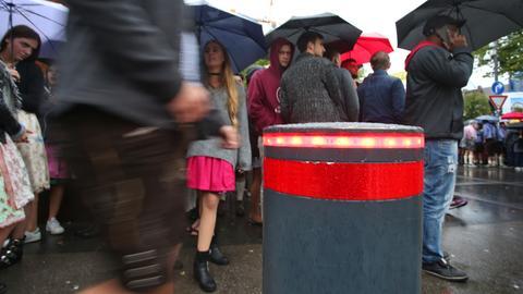Versenkbarer Poller, Menschen mit Regenschirmen