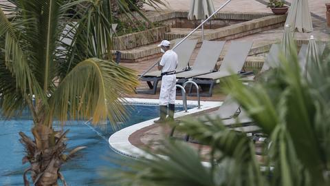 Ein Mitarbeiter steht am menschenleeren Pool in Teneriffa