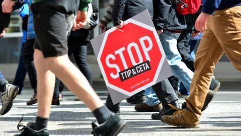 """Demonstrantin trägt ein Schild mit """"Stop TTIP und CETA"""""""