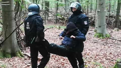 Polizisten tragen einen Waldbesetzer weg.