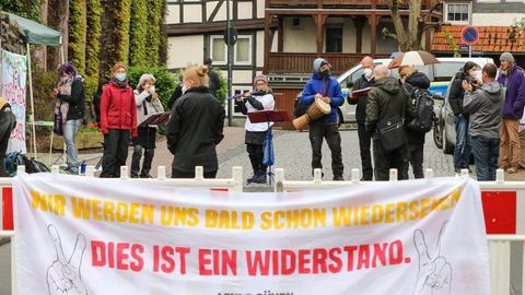 """Rund ein Dutzend Menschen steht auf einer abgesperrten Straße, davor ein Transparent mit der Aufschrift """"Wir werden uns bald schon wiedersehen - dies ist ein Widerstand"""""""