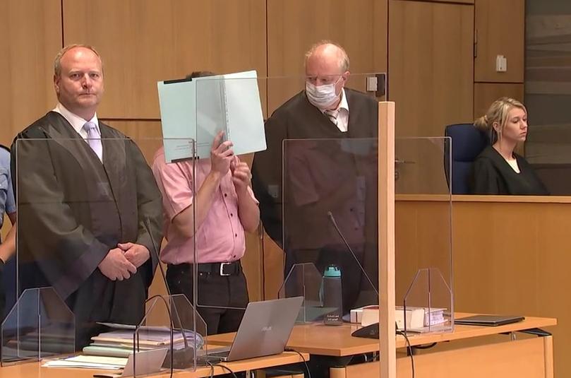 Einer der Angeklagten (Mitte) beim Prozessauftakt im August