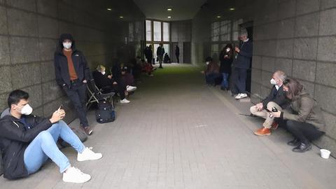 Reporter sitzen und stehen neben dem Eingang zum Gericht.