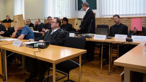 Fünf mutmaßliche, unter anderem wegen Zwangsprostitution angeklagte Bordellbetreiber haben ihre Gesichter verdeckt und sitzen mit ihren Anwälten auf den Anklagebänken.