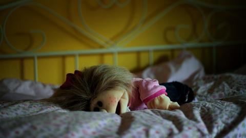Eine Puppe, die auf einem Kinderbett liegt.