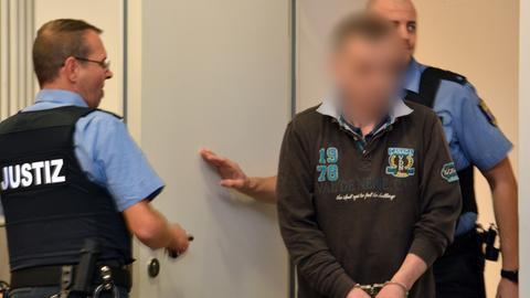 Der Angeklagte in Handschellen vor Gericht mit zwei Polizisten