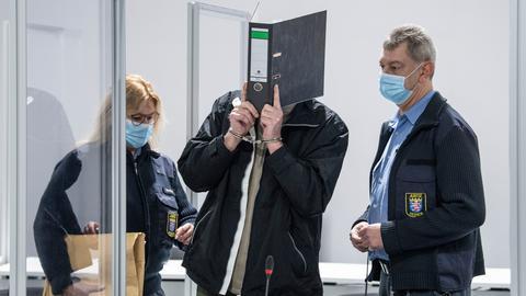Der Angeklagte steht zwischen zwei Justizbeamten und verdeckt sein Gesicht mit einem Ordner