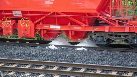 Weißes Pulver rieselt aus einem Güterzug-Waggon.