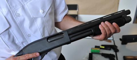 Beamter zeigt eine beschlagnahmte Pumpgun