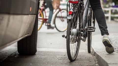 Radfahrer stehend neben Auto.