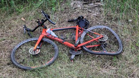 Das zerbeulte Fahrrad liegt im Gras.