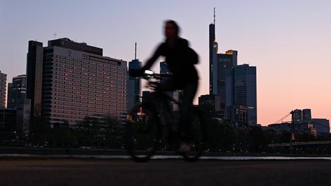 Ein Radfahrer vor Hochhäusern.