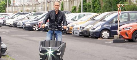 Moritz Nohlen sitzt auf seinem wiedergefundenen Lastenrad und fährt damit auf einem Parkplatz. Im Hintergund ist unscharf ein Gefängnis zu sehen.