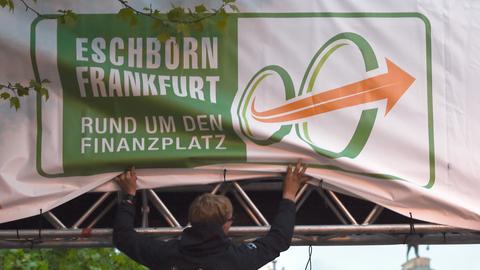 Ein Mann hängt ein Radrennen-Plakat ab