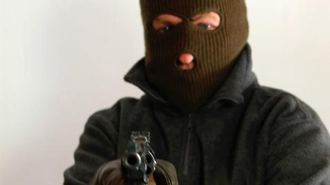 Maskierter Räuber mit Pistole