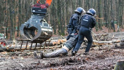 Polizisten schleifen einen Aktivisten im Dannenröder Forst weg.