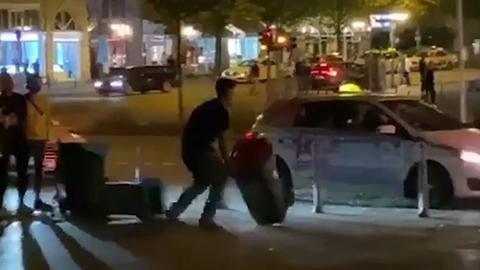 Mann schnappt sich Mülltonne und wirft sie auf die Straße vorm Opernplatz