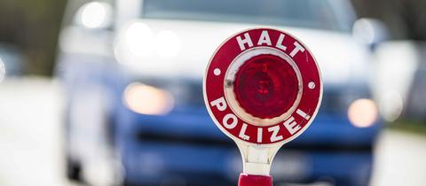 """Polizeikelle mit Aufschrift """"Halt"""" vor einem Auto"""
