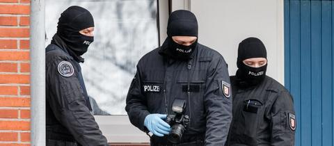 Beamte eines Spezialeinsatzkommando (SEK) der Polizei stehen während einer Razzia vor einer Wohnung.
