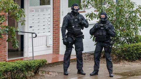 Beamte eines Spezialeinsatzkommando (SEK) der Polizei stehen während einer Razzia vor einem Hauseingang.