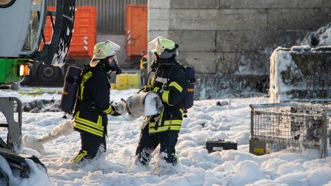 Feuerwehr steht knietim Löschschaum.