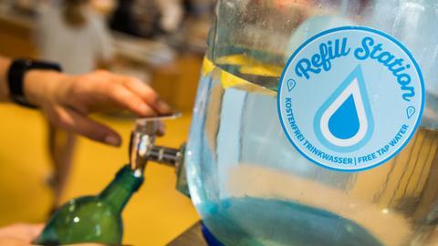 Eine Kundin füllt sich in einem Bio-Supermarkt in Frankfurt kostenlos Trinkwasser in die eigene Glasflasche.