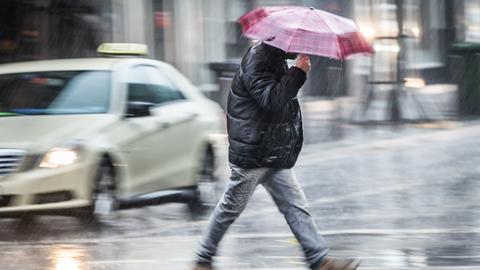 Ein Mann mit Regenschirm beeilt sich, bei strömenden Regen eine Straße in der Frankfurter Innenstadt zu überqueren.