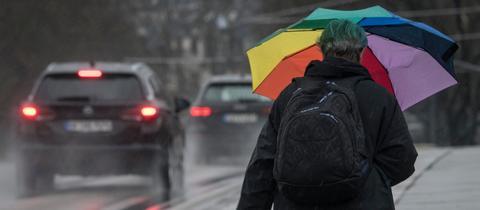 Mit einem bunten Schirm schützt sich eine Frau in Frankfurt gegen Regen.