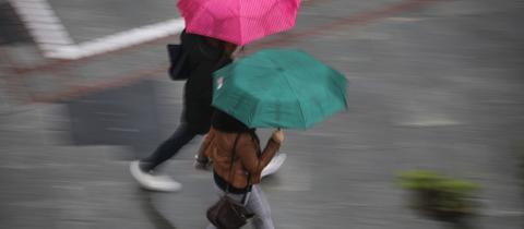 Zwei Passantinnen mit Regenschirm