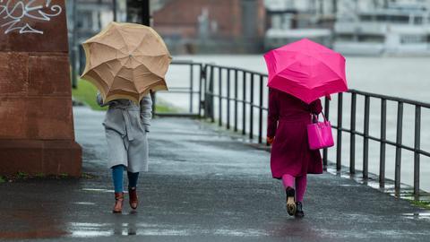 Zwei Frauen gehen mit Regenschirmen in Frankfurt am Mainufer entlang.
